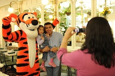 Chilean miner rescuer Patricio Alejandro Sepulveda Munoz (right) joins his daughter Esperanza Anais Sepulveda (left, age 2) and Disney character Tigger as his wife, Yessica Vivian Sepulveda (foreground) takes a souvenir photograph at Walt Disney World Resort