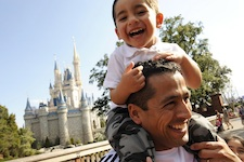 Chilean miner rescuer Roberto Cristian Rios is all smiles as he gives his son, Robert Alex Rios (age 4), a ride atop his shoulders in front of Cinderella Castle at the Walt Disney World Resort