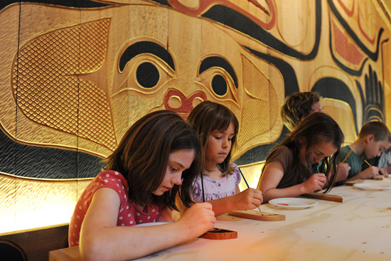 Children paint a wooden feather to add to a special Disney Cruise Line totem pole.