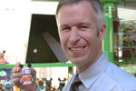 Disney Parks Blog author and Merchandise Communications Manager Steven Miller places one of the well-traveled Vinylmations in the display case at D-Street.
