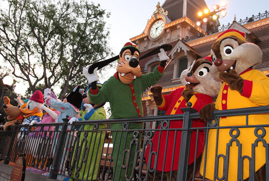 Goofy and his friends in their pajamas atop the Main Street Train Station at Disneyland Park waving goodbye to guests.