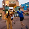 Runners receive a high-five from Pluto during their run at Disney's Hollywood Studios.