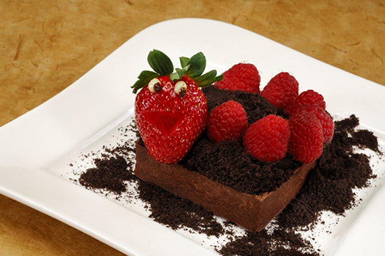 "The Worms & Dirt Tart Topped with a Smiling Strawberry, Fresh Raspberries, and Chocolate Cookie ""Dirt"" Crumbs"
