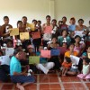 These artisans are holding their certificates of completion after completing a training session on how to create the plush