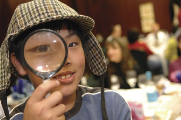 A Young Traveler with Adventures by Disney Looks Through a Magnified Glass