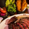 Double Joint Cowboy Cut Rib-Eye Steak served with roasted veggies, duck fat fries, salad and sauces from Raglan Road