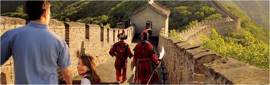 Uniformed guards walk the Great Wall of China as father looks on and a smiling daughter looks back