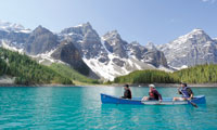 Three canoers paddling on a clear blue glacier lake framed by snow-capped mountains
