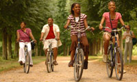 Family of four riding bikes on a forest trail during their family adventure