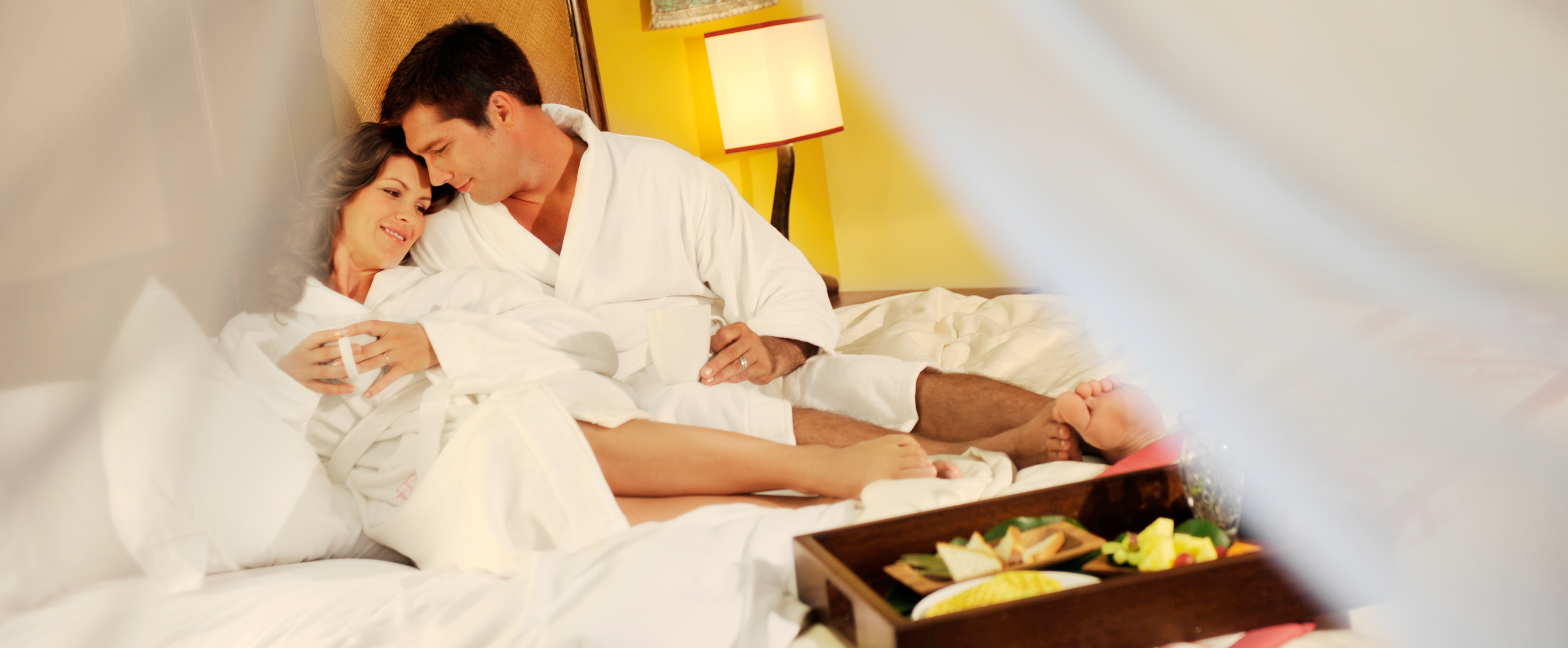 A couple unwinds in bed with room service