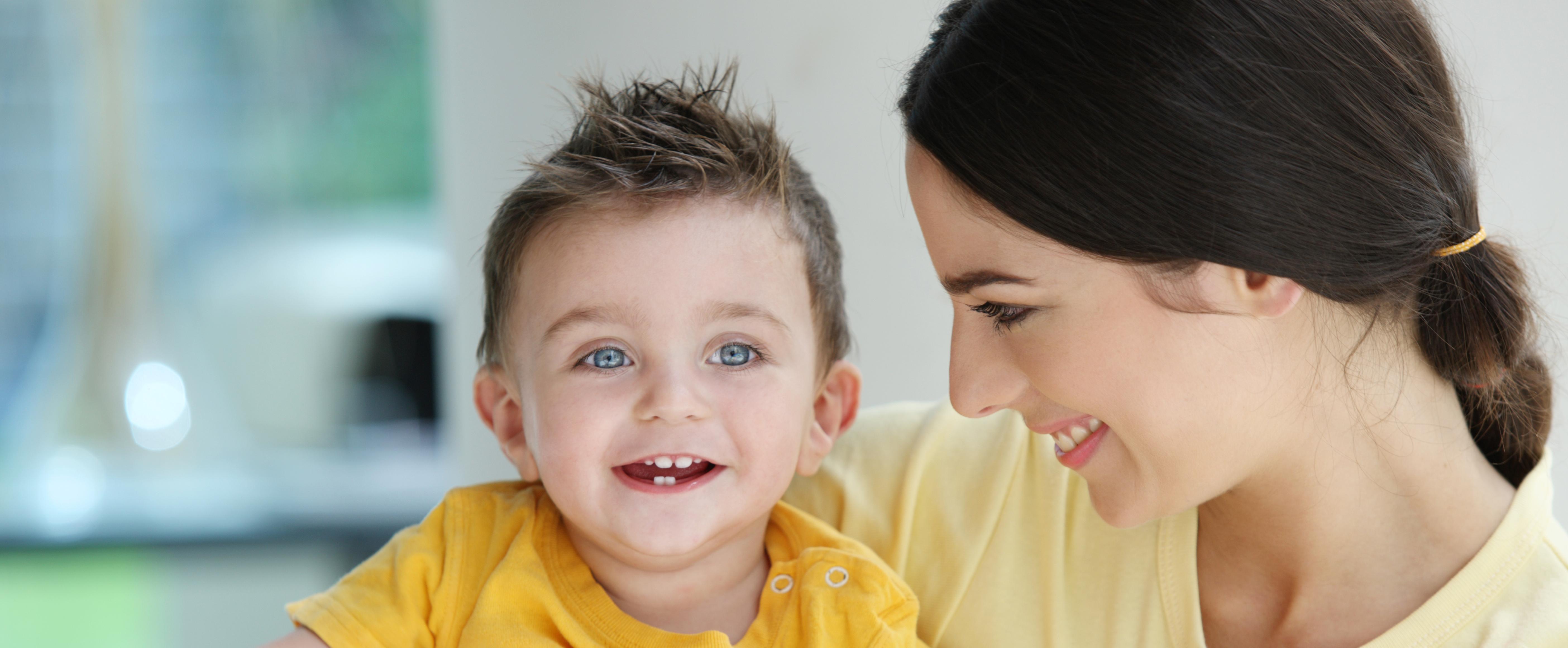 A babysitter holding a toddler