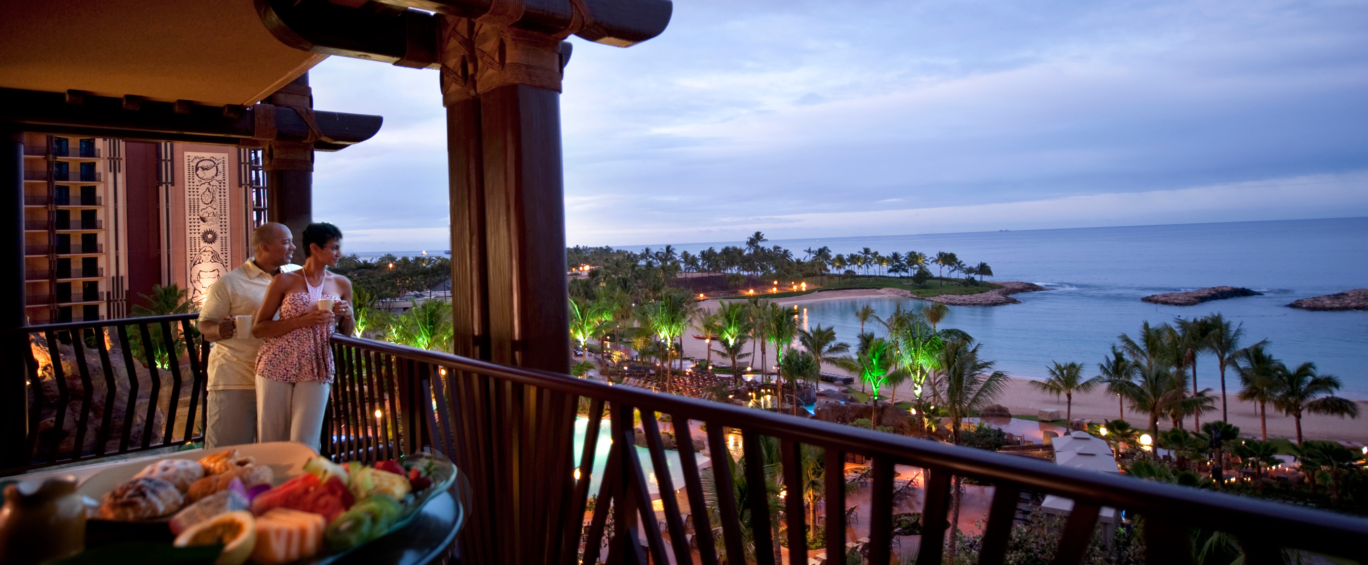 A couple looks at the ocean from the balcony of a 3-Bedroom Grand Villa
