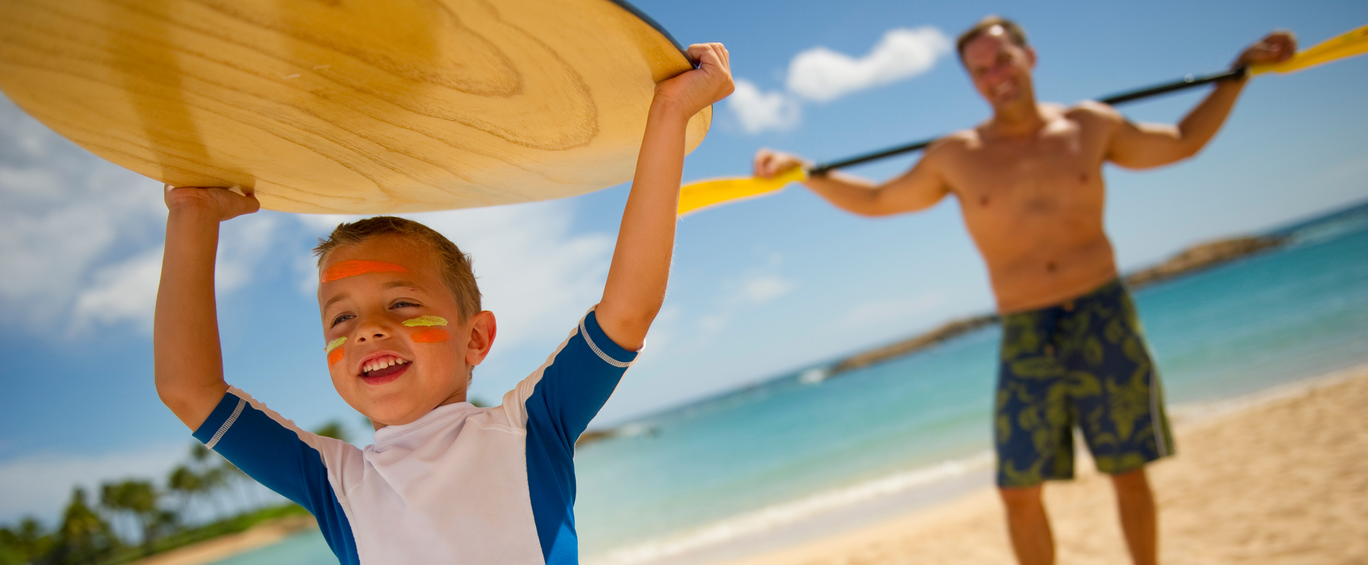 A young boy lifts a paddleboard over his head