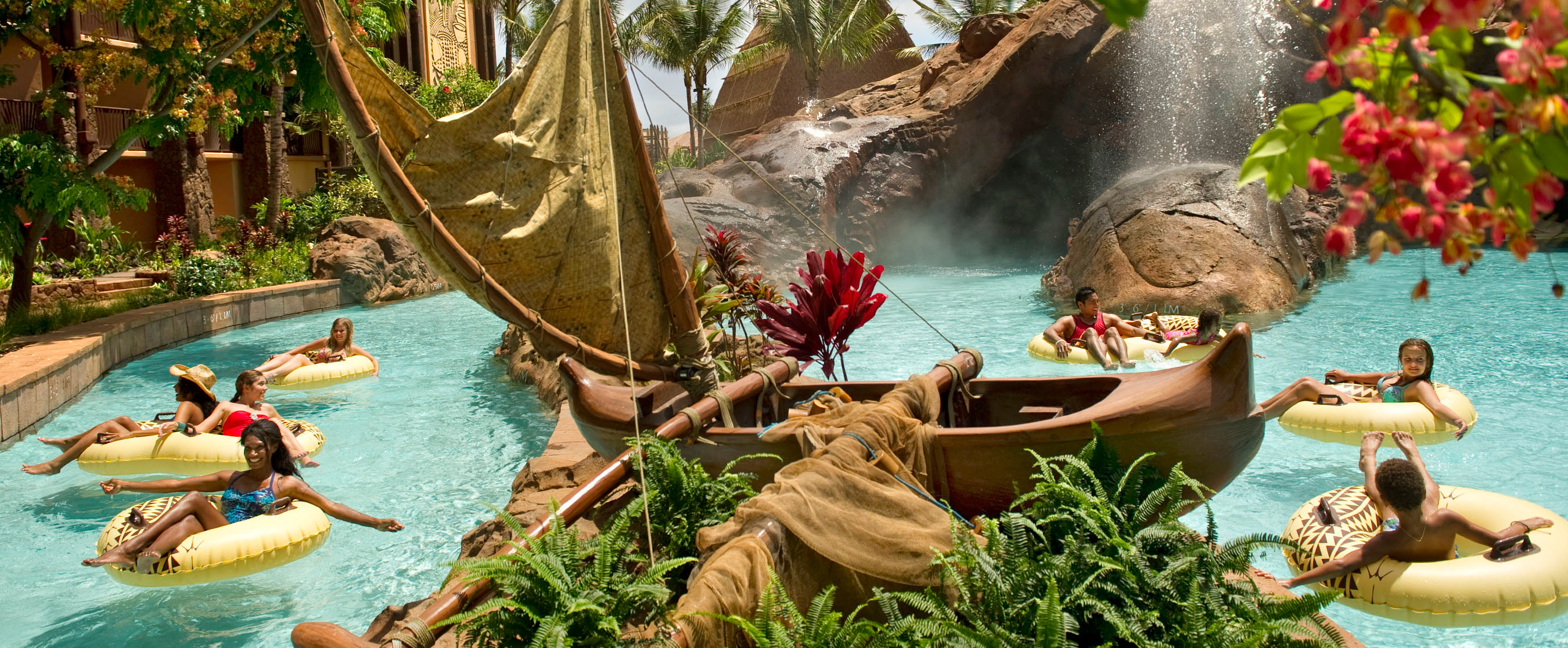 Guests tubing on the lazy river in the Aulani pool area