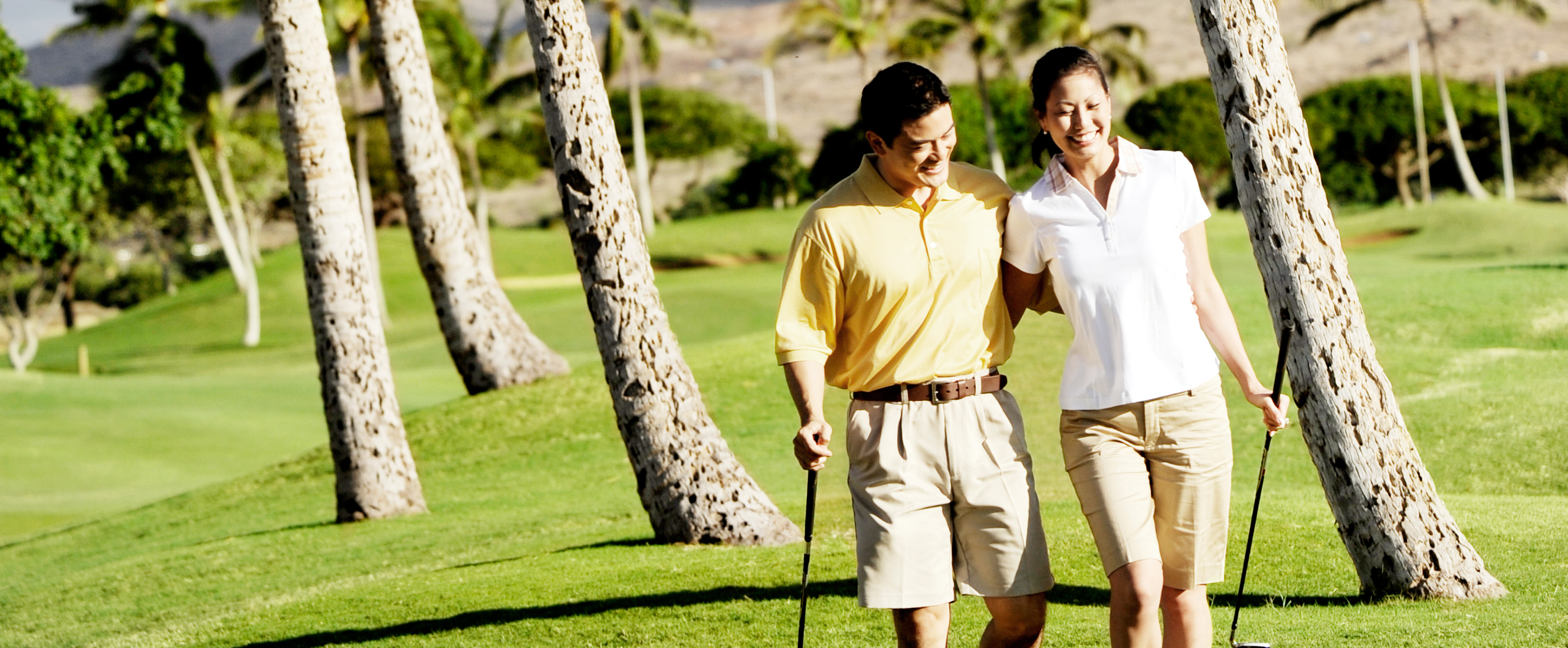 A man and woman walk across the grass with their arms around each other, each carrying a golf club