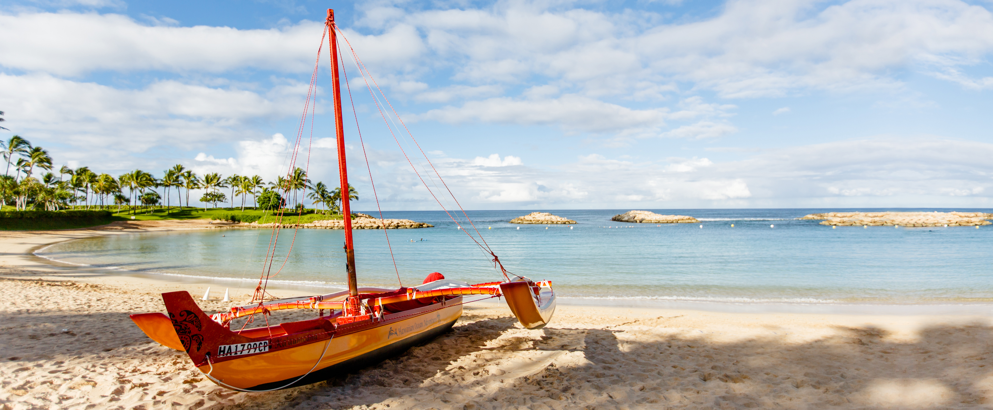 A Hawaiian Ocean Adventures sailing canoe on a sandy tropical beach, near the water's edge