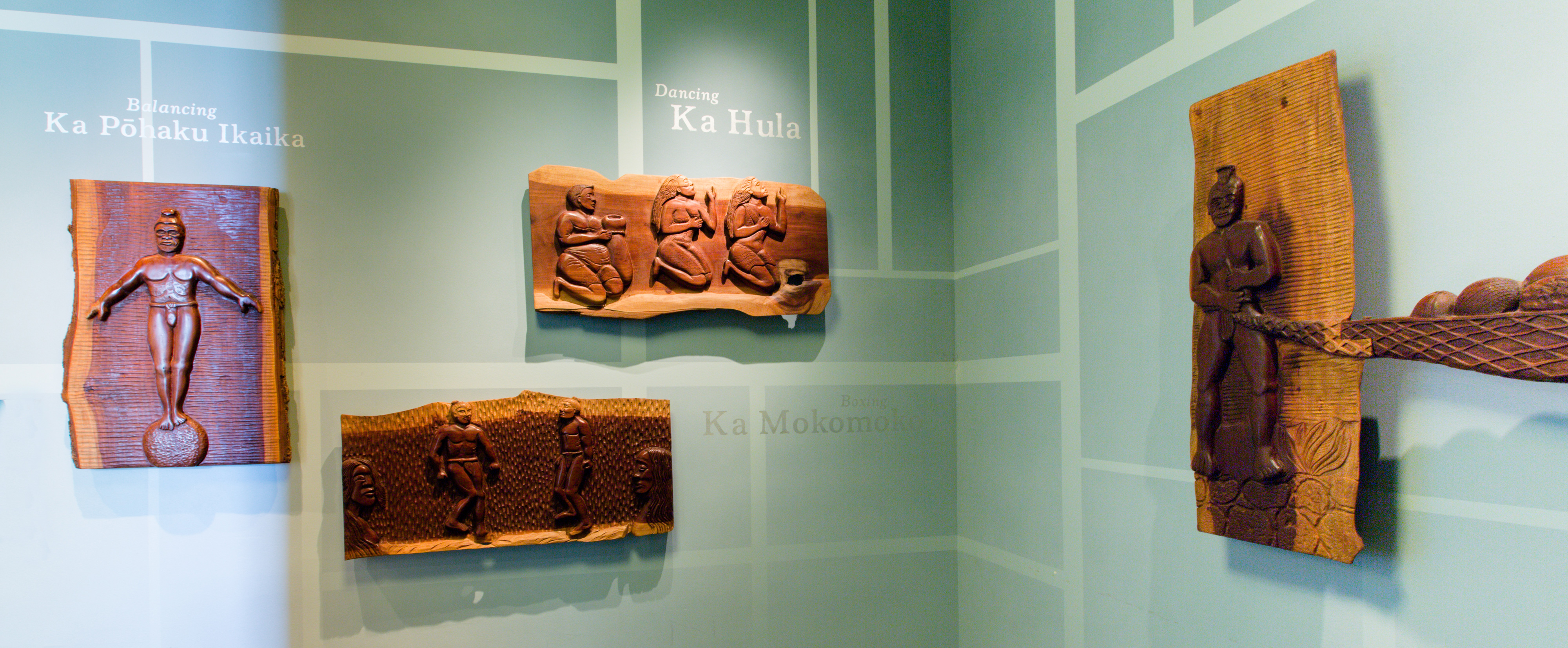 Wood relief carvings of natives engaged in various activities, with descriptive Hawaiian phrases and their English translations