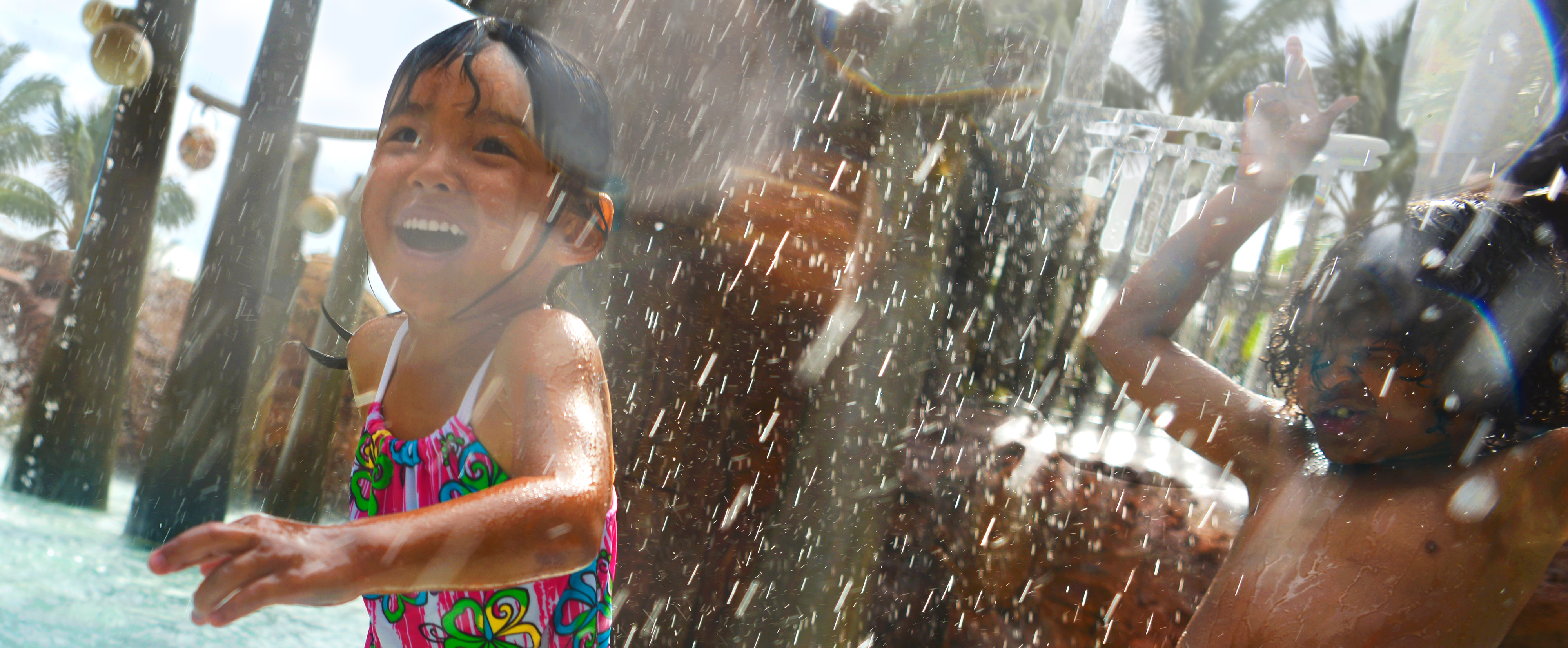 A boy and girl laugh and splash about beneath the cascading water of the Menehune Bridge play area