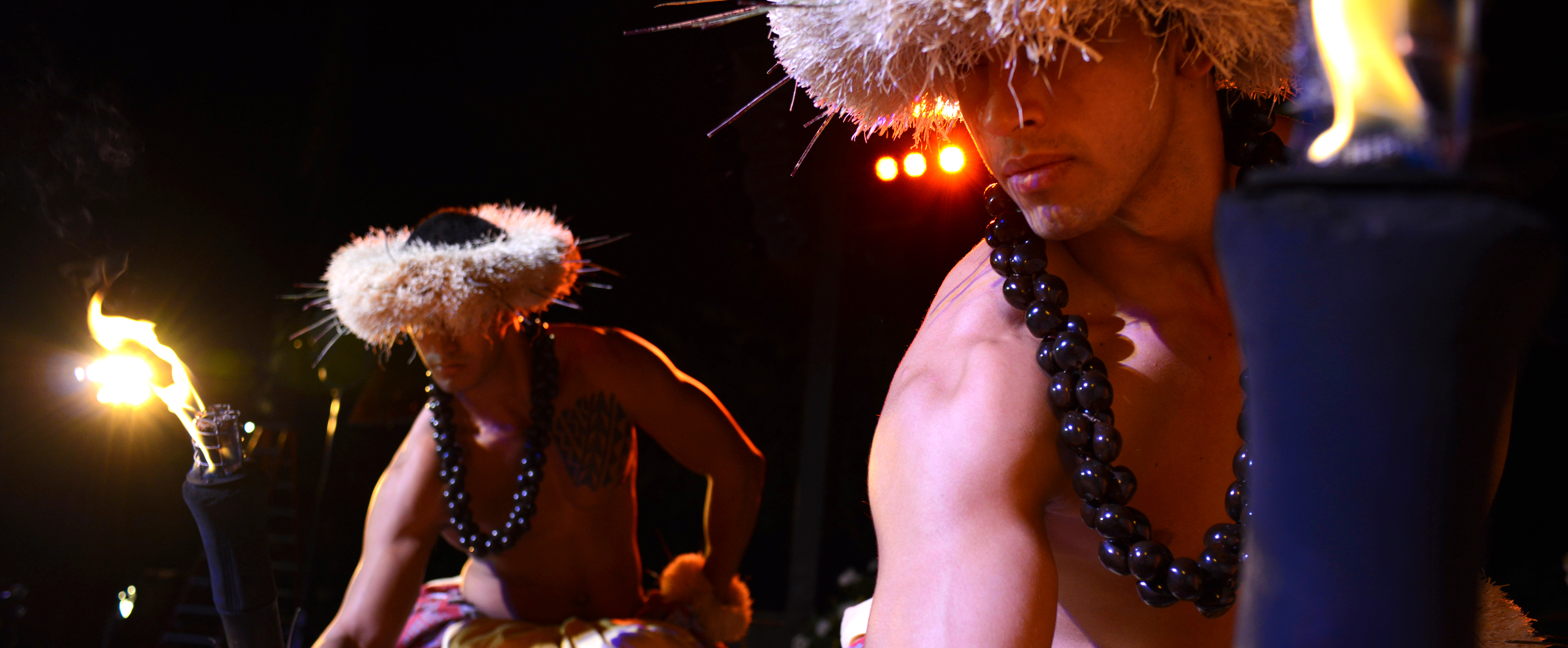 Two shirtless men wearing native headdresses and kukui nut necklaces dance with lit torches