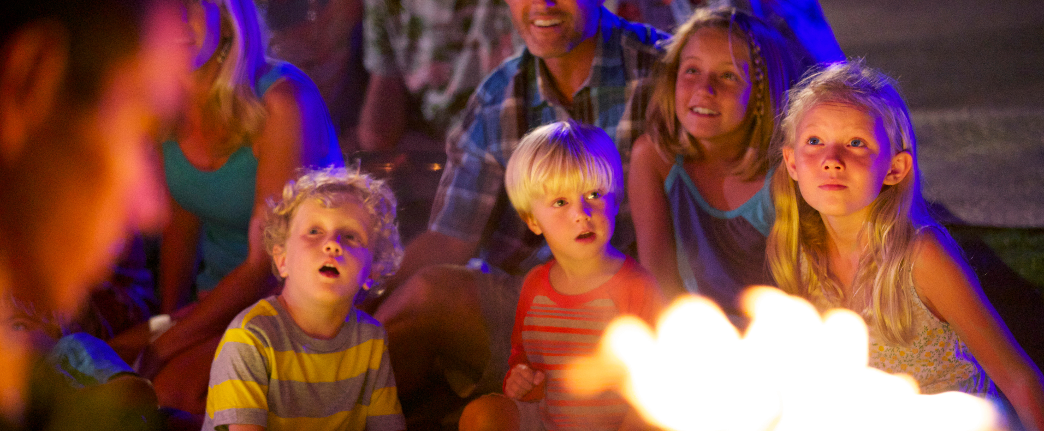 Two small boys and 2 girls watch transfixed as a man hovers near a large flame