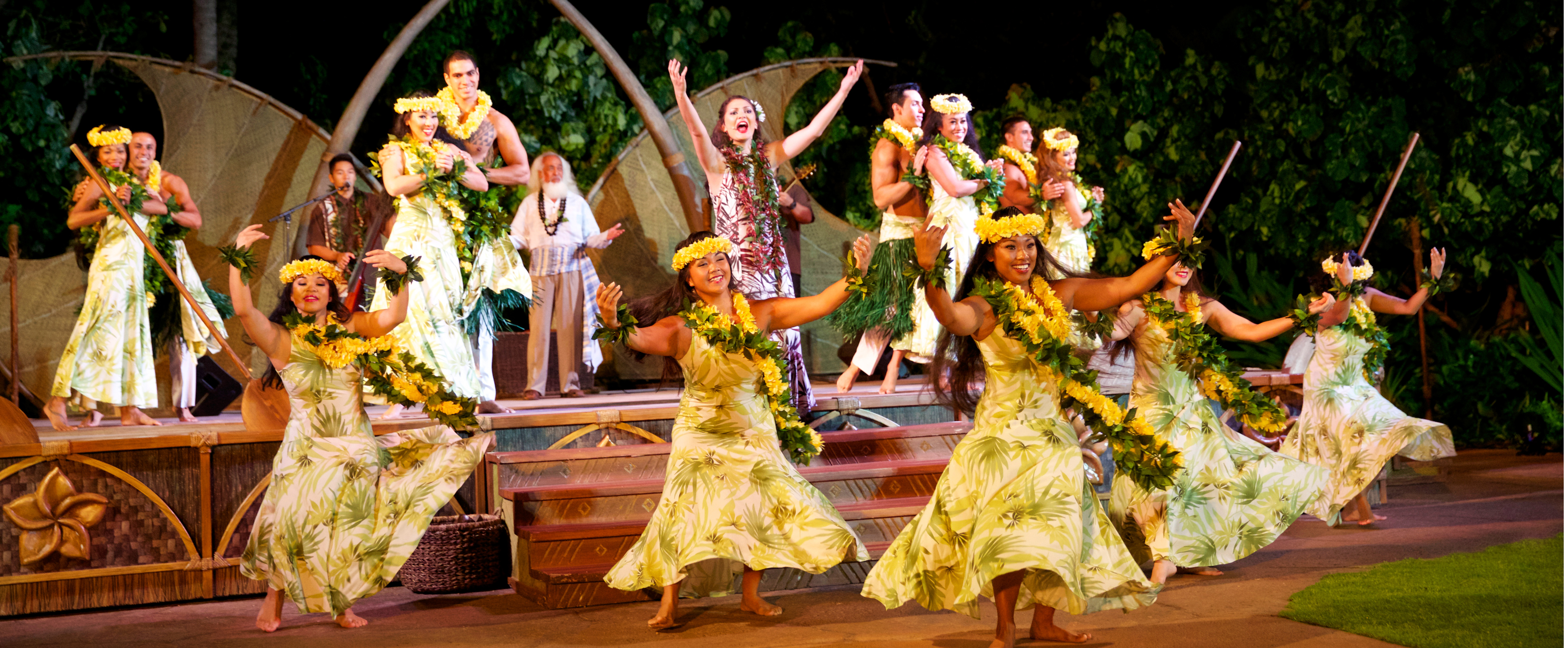 Polynesian dancers wearing palm-printed dresses, head wreaths and leis perform onstage with musicians