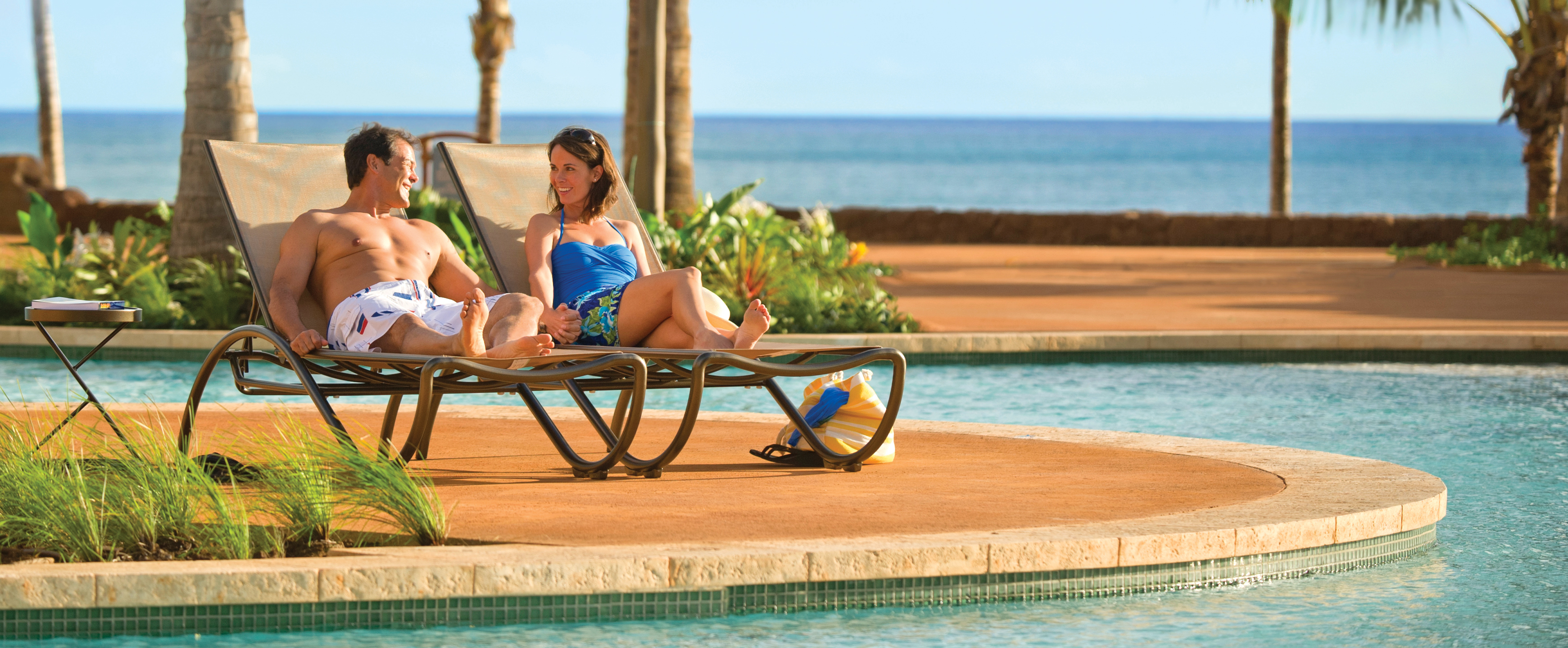 A swimwear-clad man and woman chat poolside on lounge chairs while an ocean view stretches beyond
