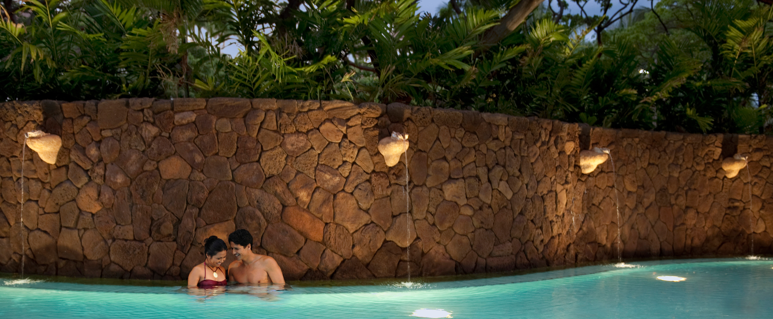 A woman and man at dusk in a pool with a high, curving rock wall accented with shell-like water spouts