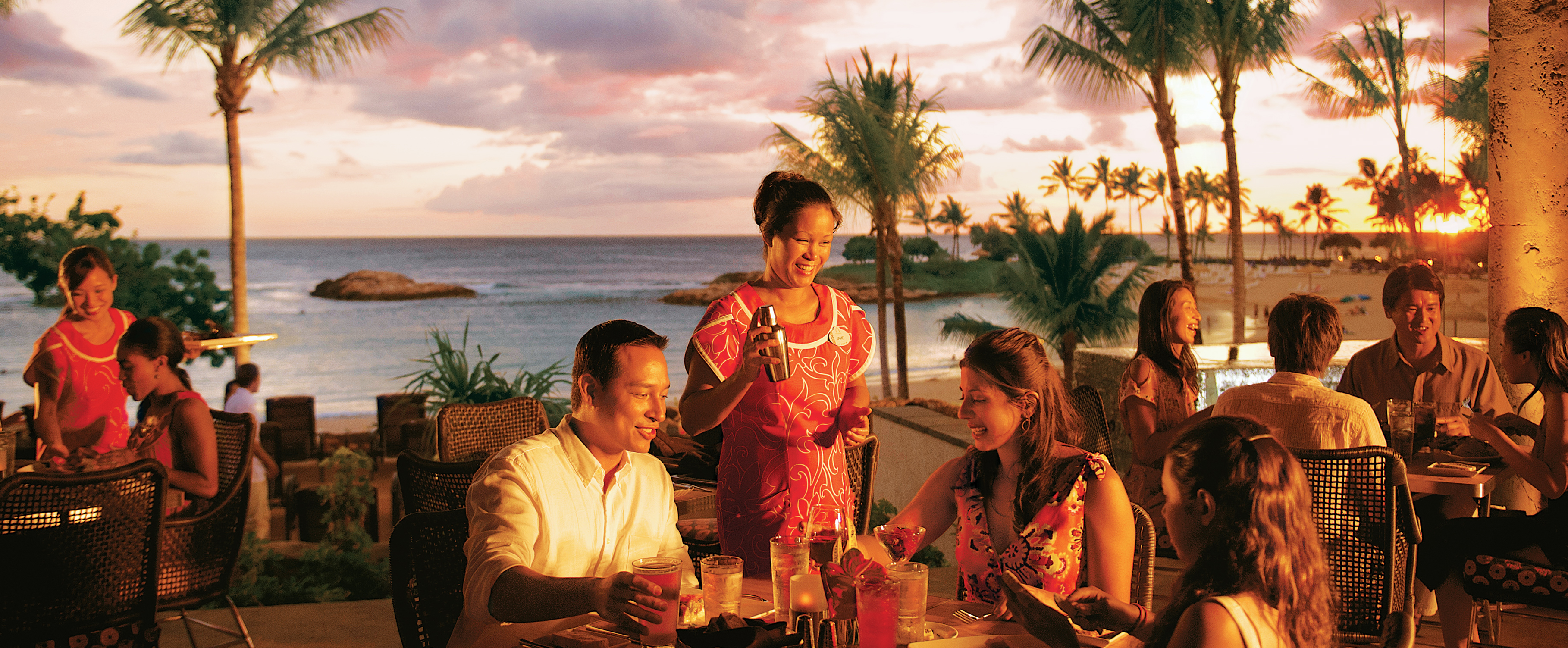 A friendly server tends to a father, mother and daughter at an outdoor table with sunset ocean views