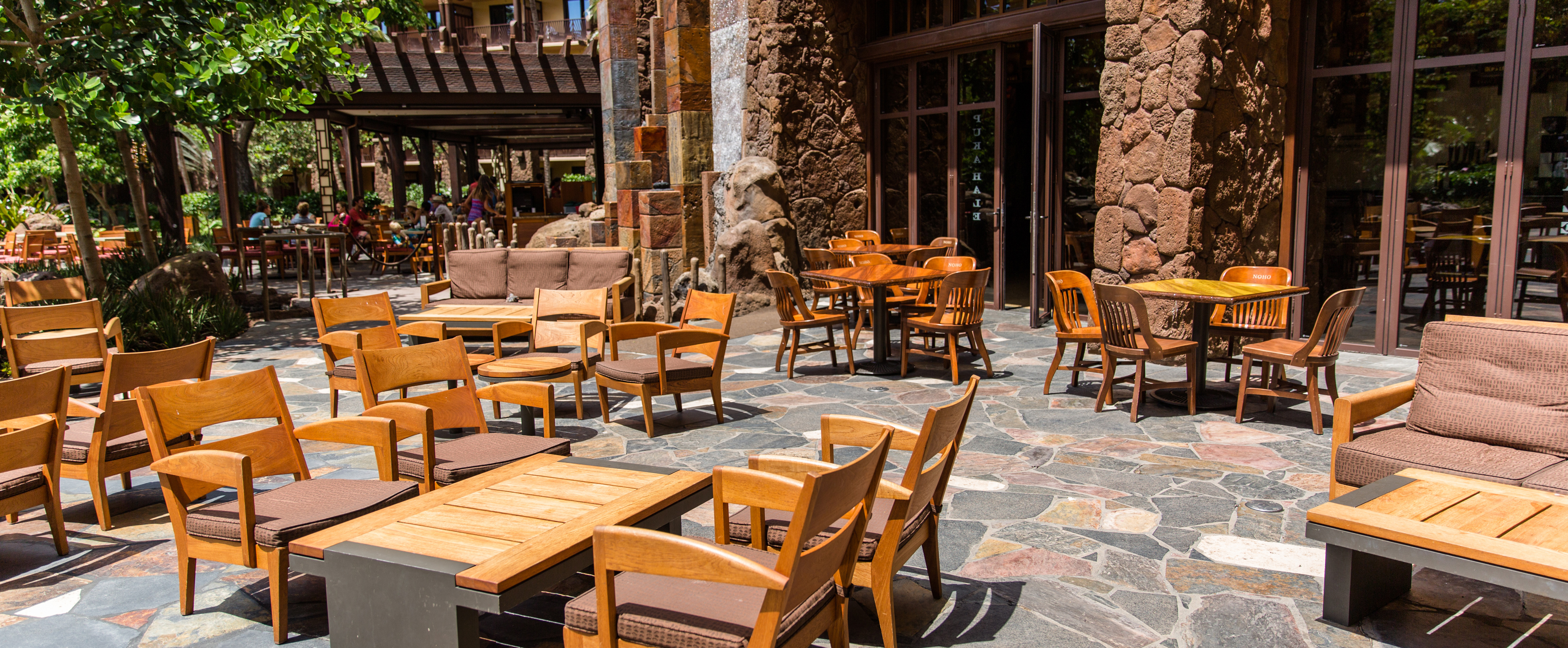 Outdoor tables and 2 couches on a flagstone-paved patio