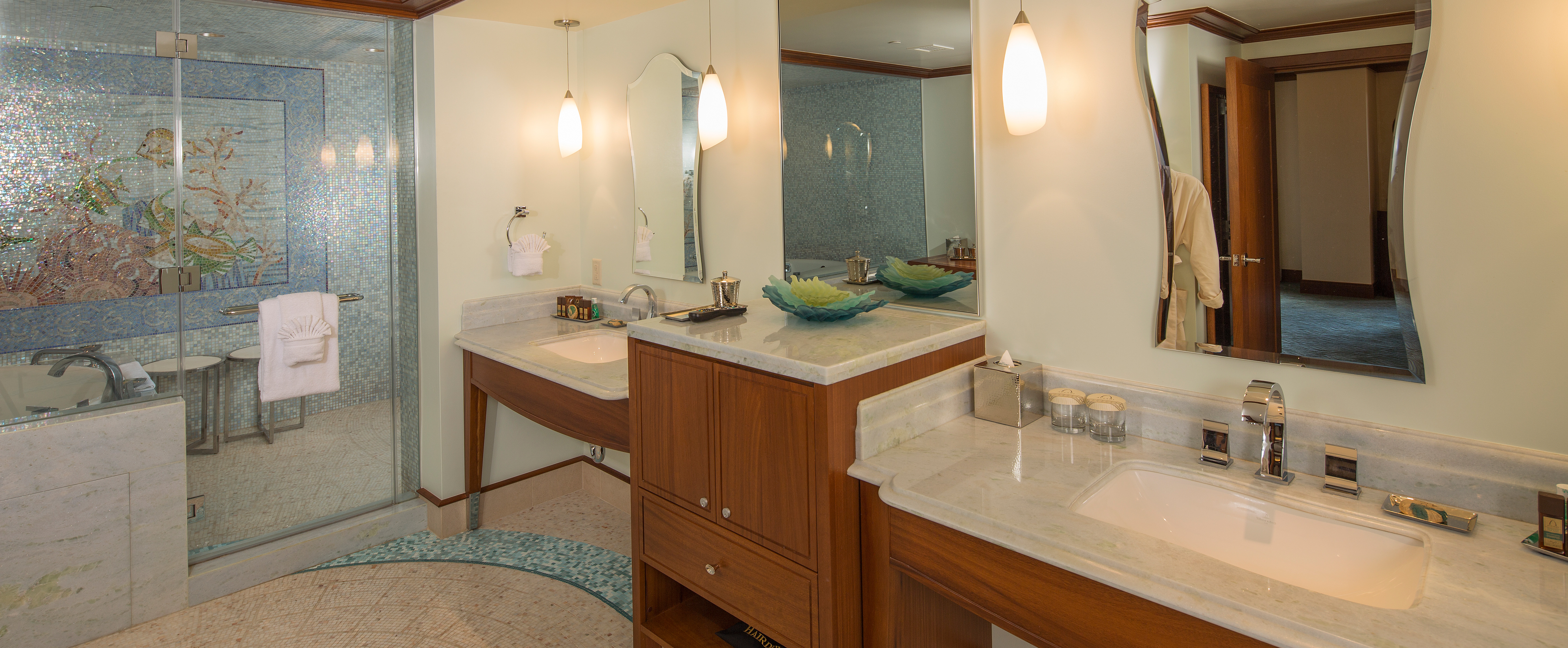 The master bathroom features 2 sinks and a large walk in shower and tub area with tiled mosaic art