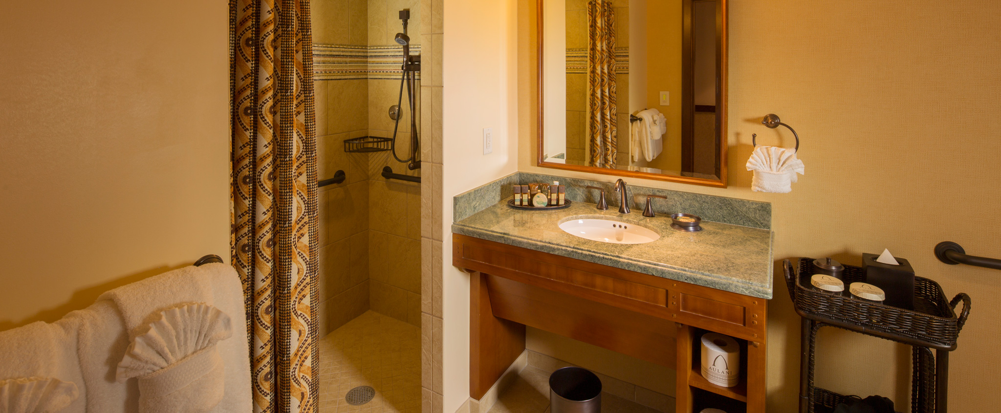 A bathroom in a 2-Bedroom Suite has a sink, tiled shower with curtain and washcloths folded in fan shapes