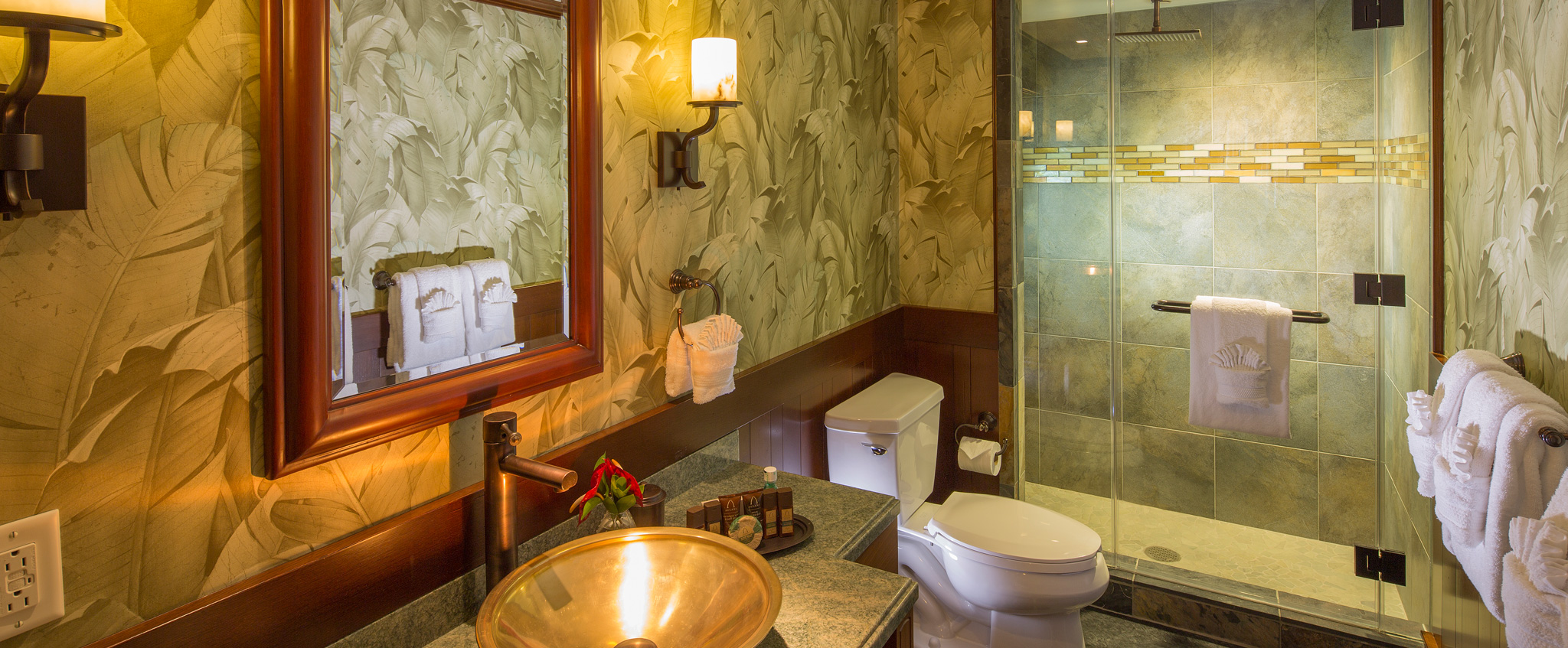 A bathroom in a 2-Bedroom Suite features palm tree wallpaper, walk-in shower, a toilet and a sink console