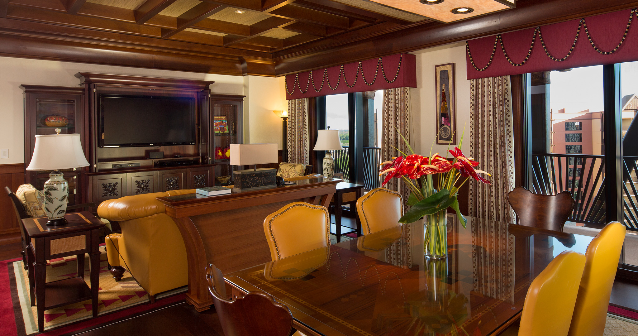 The living area of the 2-Bedroom Suite includes an entertainment center, seating area and dining table