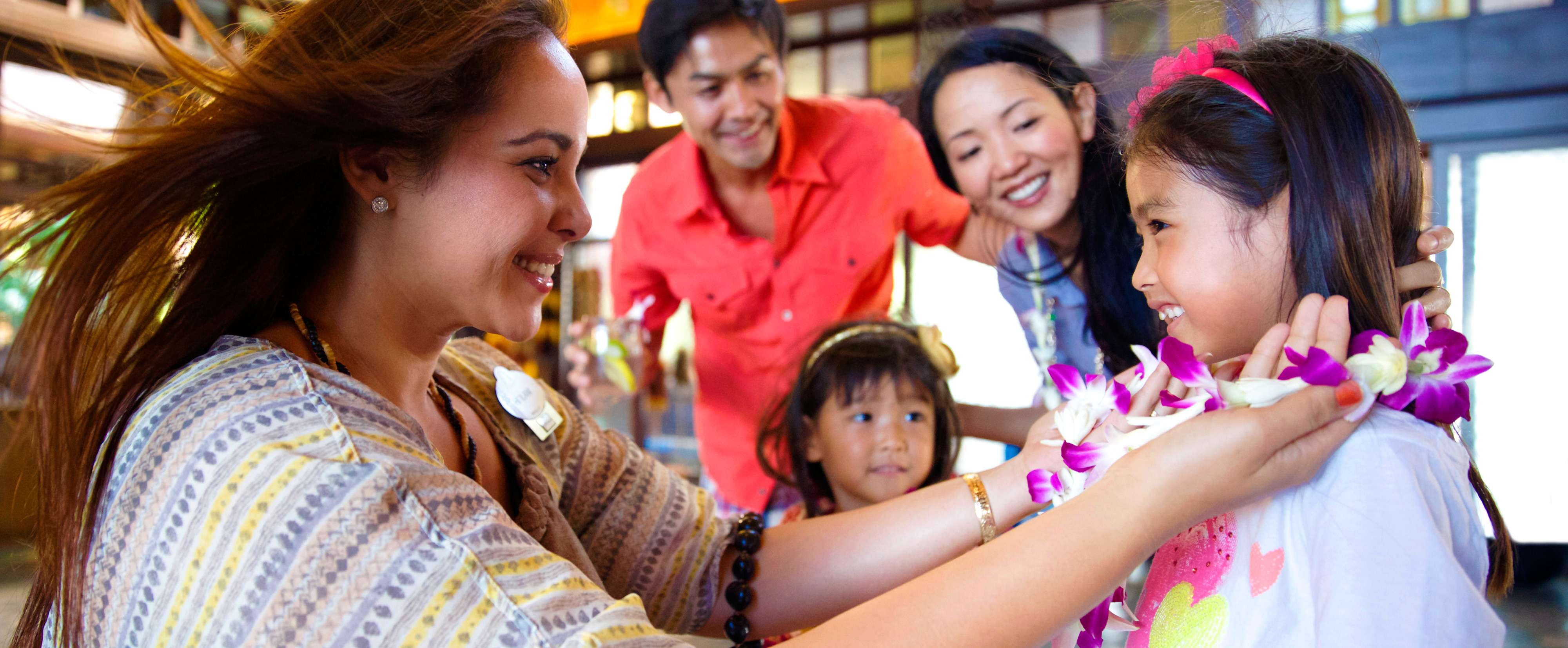 A family receives leis in the Lobby at Aulani