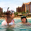 Two young women and a young man with masks and snorkel laugh as they enjoy the ocean at Aulani
