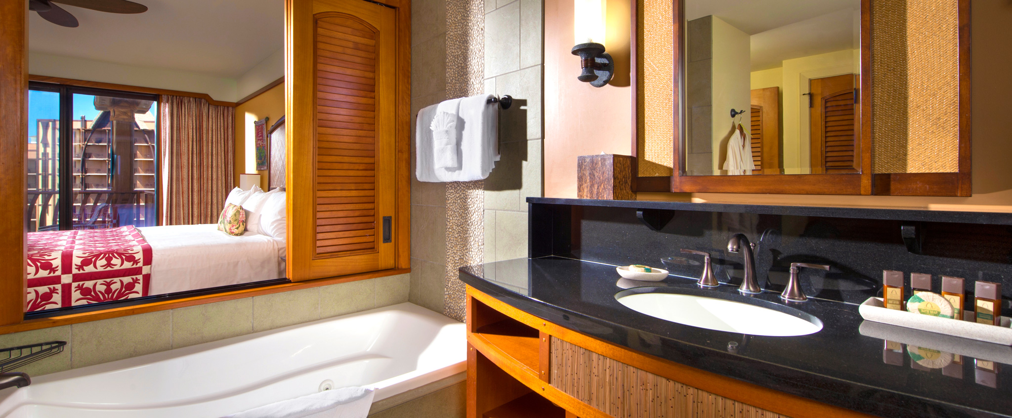 The bathroom of the 1-Bedroom Villa has a dark granite countertop and a bathtub with view of the bedroom