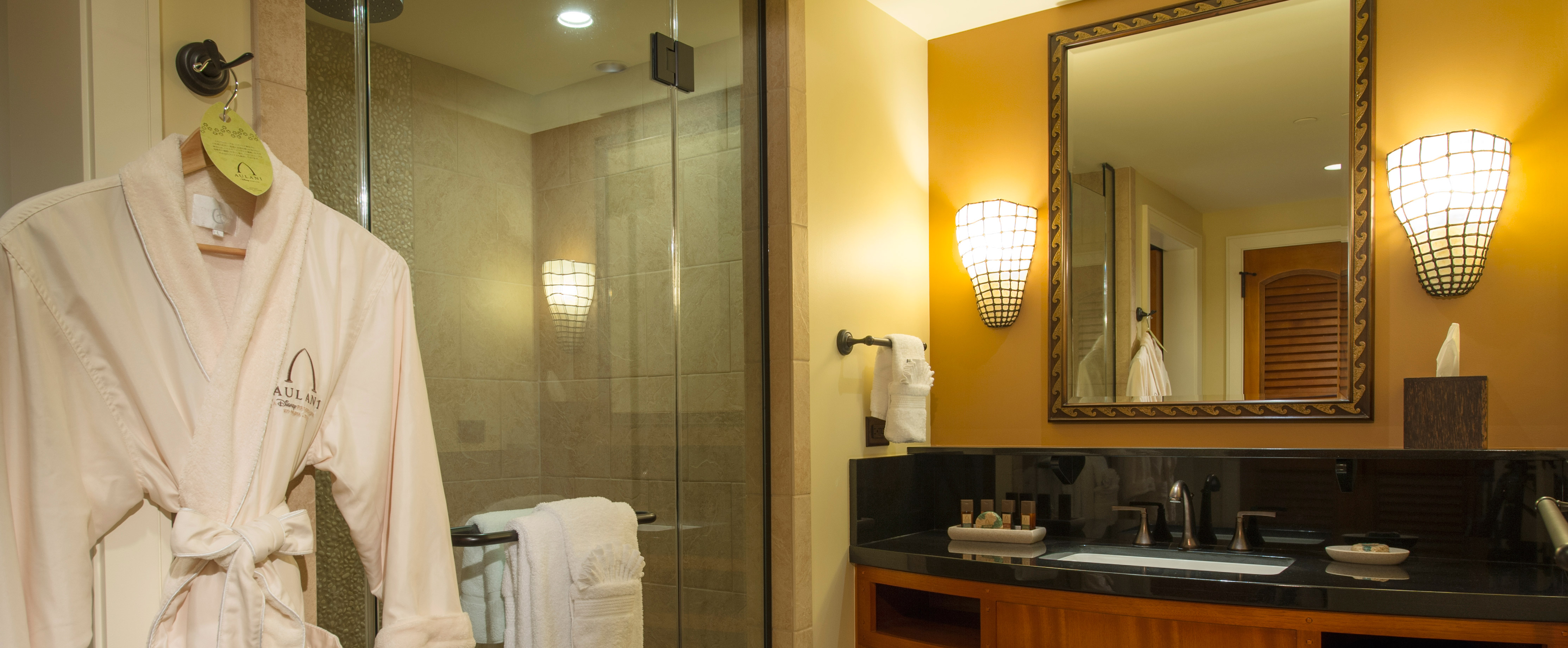 An Aulani terry robe hanging beside a glass-door shower next to a vanity with illuminated wall sconces