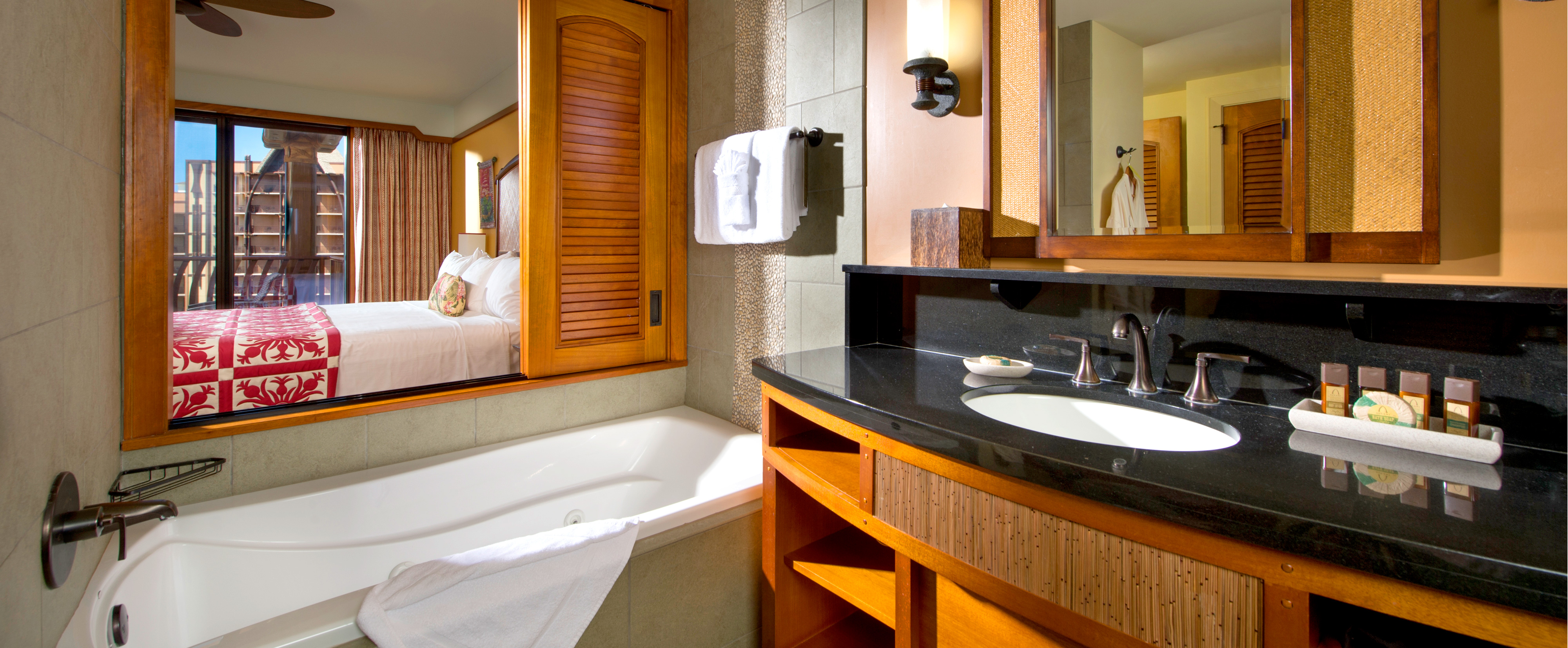 A master bathroom with whirlpool tub looks on an adjoining bedroom through a large wooden-shuttered window