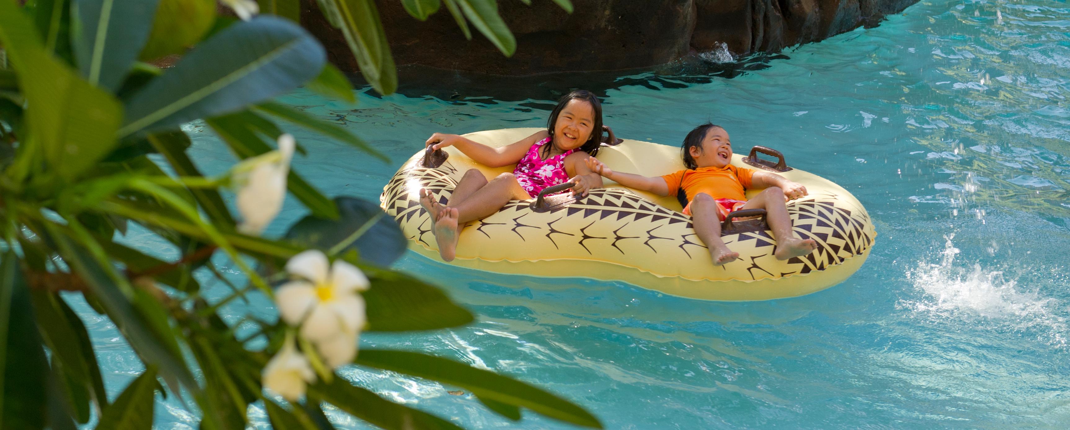 アウラニの流れるプールで 2 人乗りのチューブに乗って遊ぶ子供たち