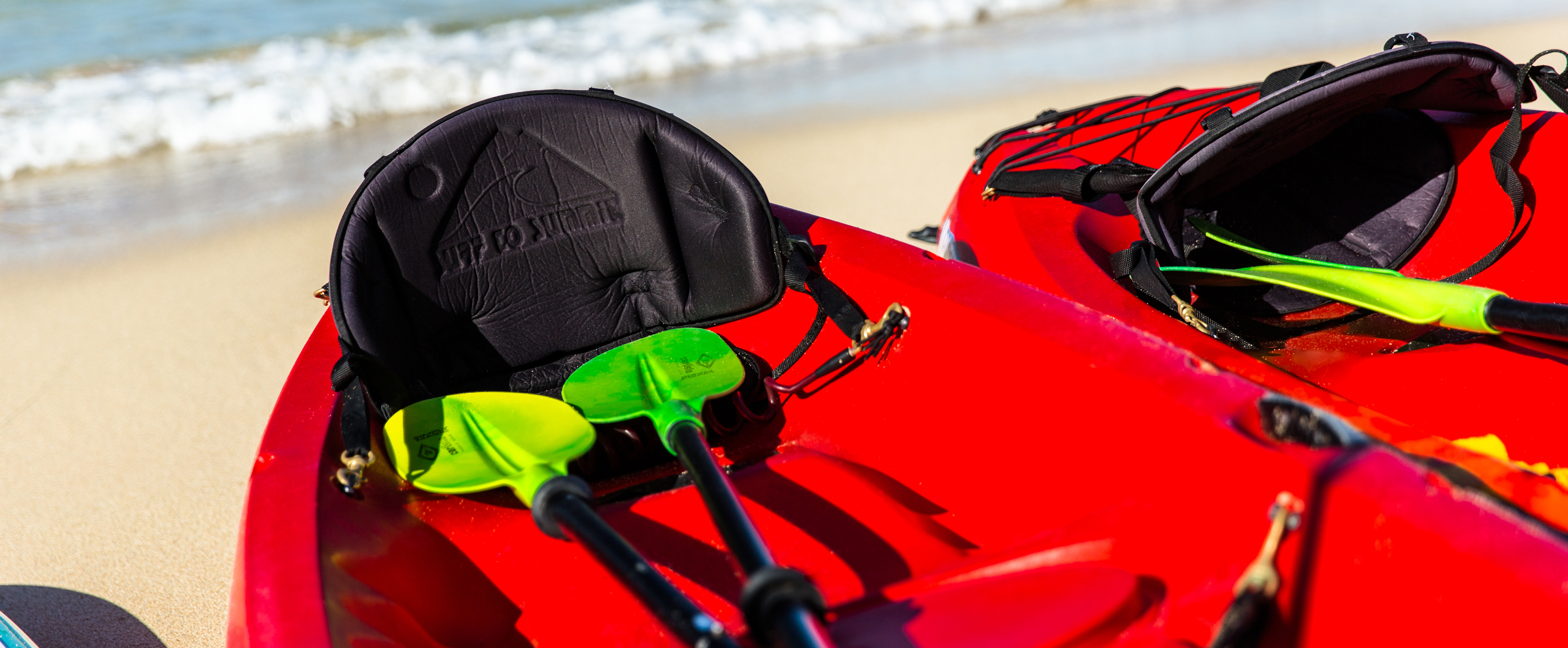 Two bright-red kayaks with paddles on the shore of a sandy beach