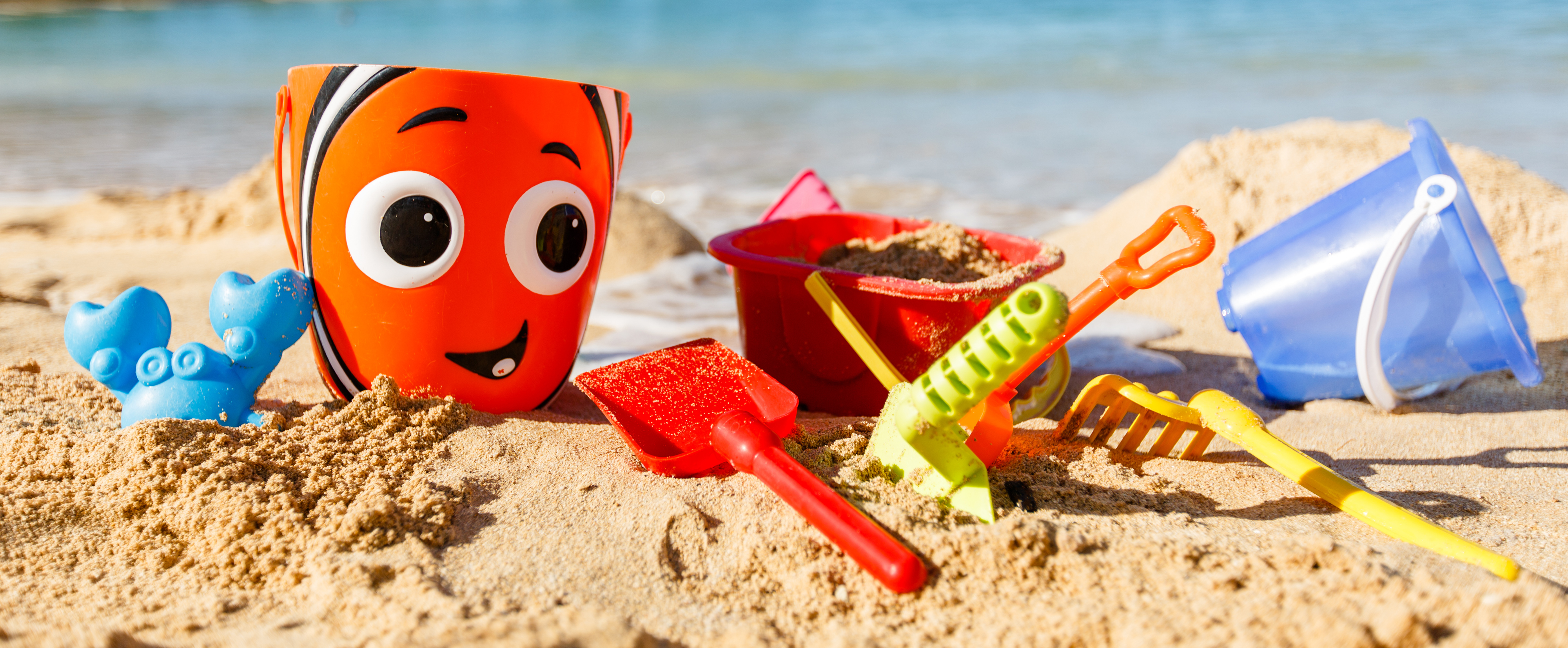 Colorful sand toys on the beach, including a Nemo bucket, a blue crab and various shoveling tools