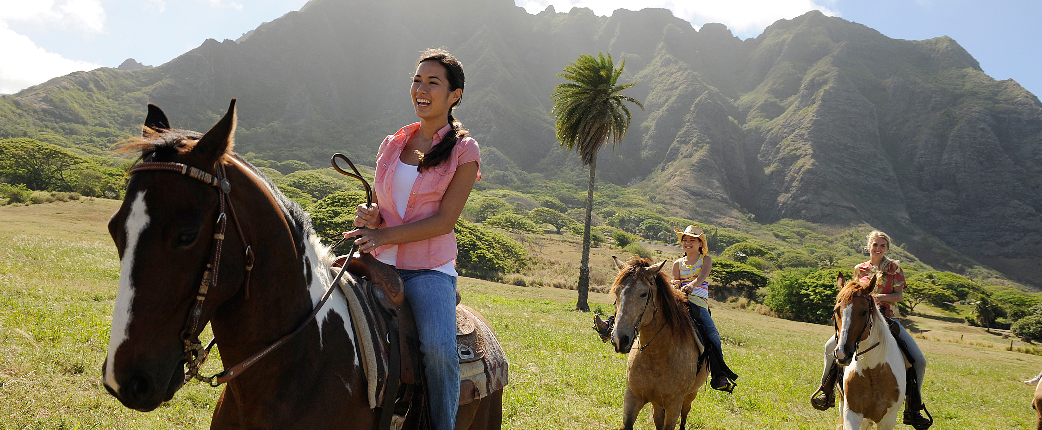 Two teen girls and a tween girl ride horses along a grassy plain with mossy mountains looming beyond