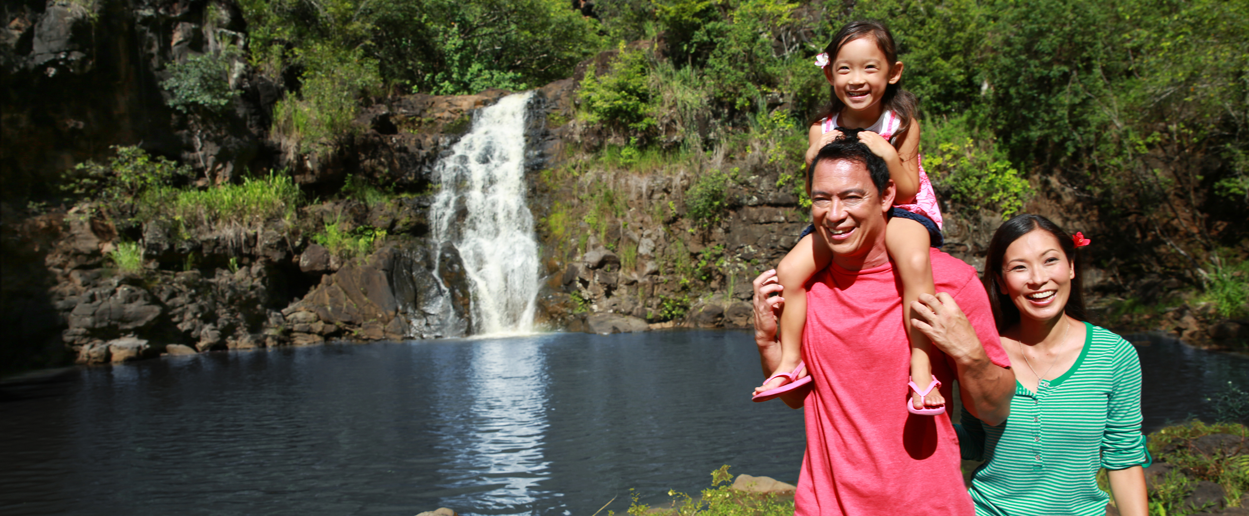 A little girl sits on her dad's shoulders while her parents smile in front of a lake with a waterfall