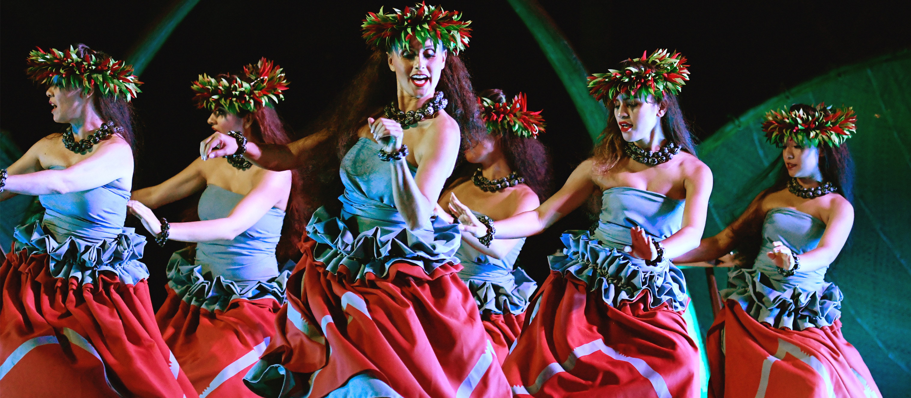 A group of Hawaiian women in traditional outfits and leafy head dresses perform an island dance at the Ka Wa'a Luau.
