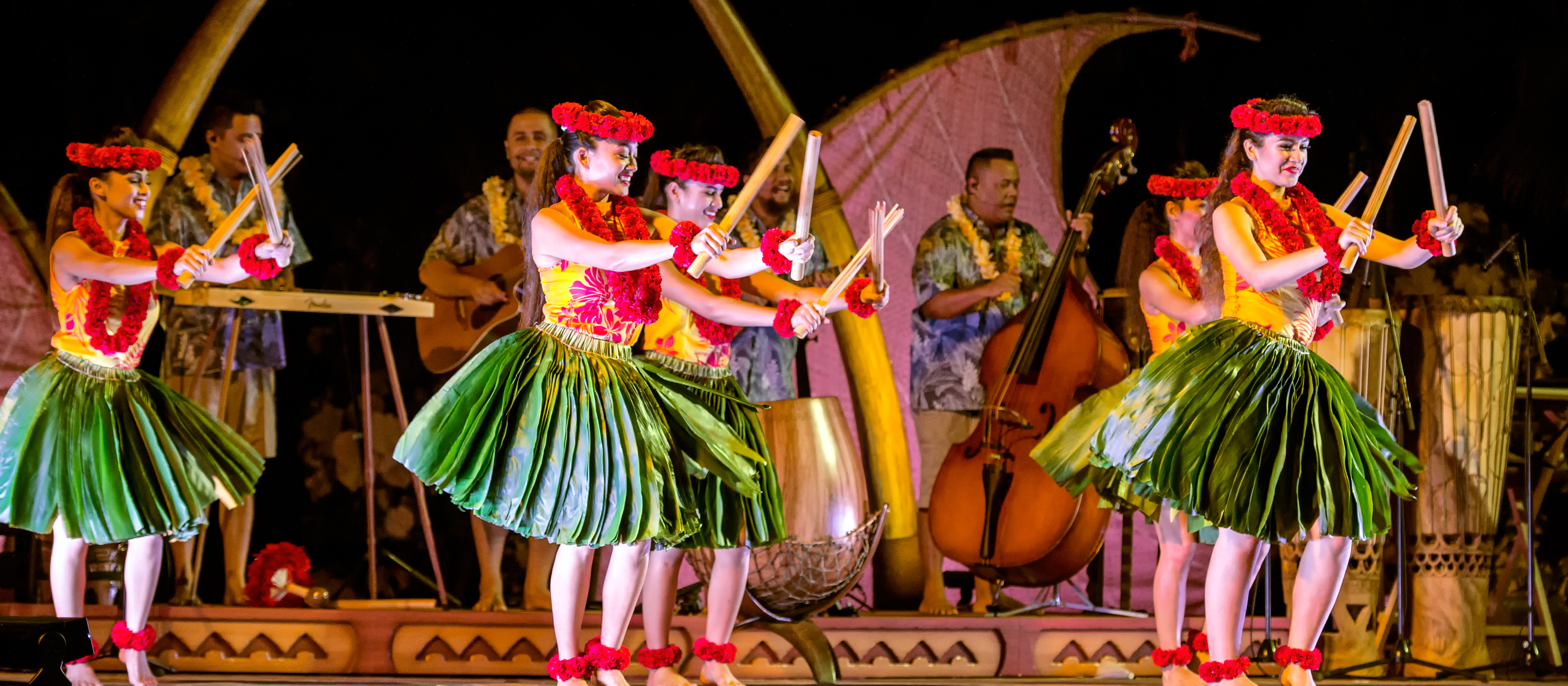 Hawaiian dancers in skirts made of leaves, leis and headdresses perform a dance using bamboo sticks to accompany the band behind them.