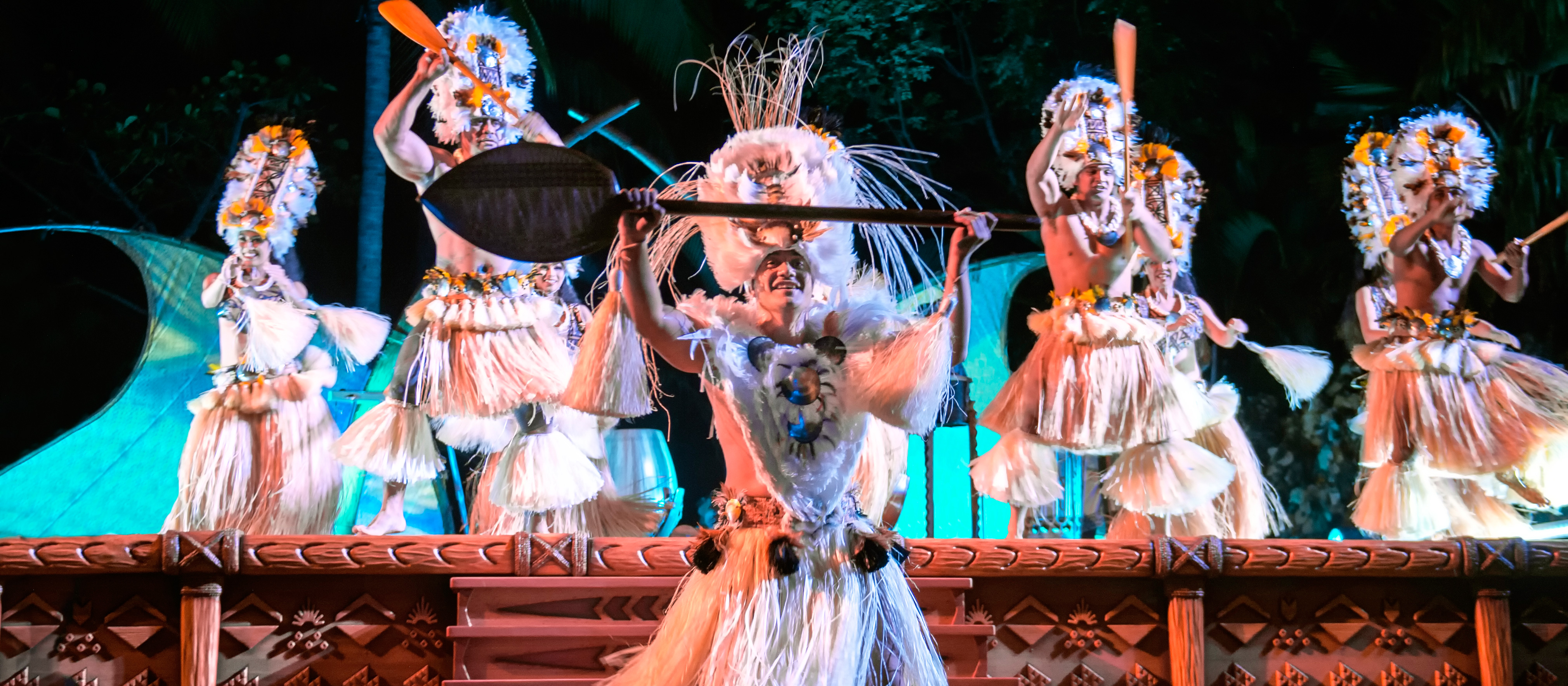 Male dancers in ornate Hawaiian grass skirts perform a traditional dance using oars.