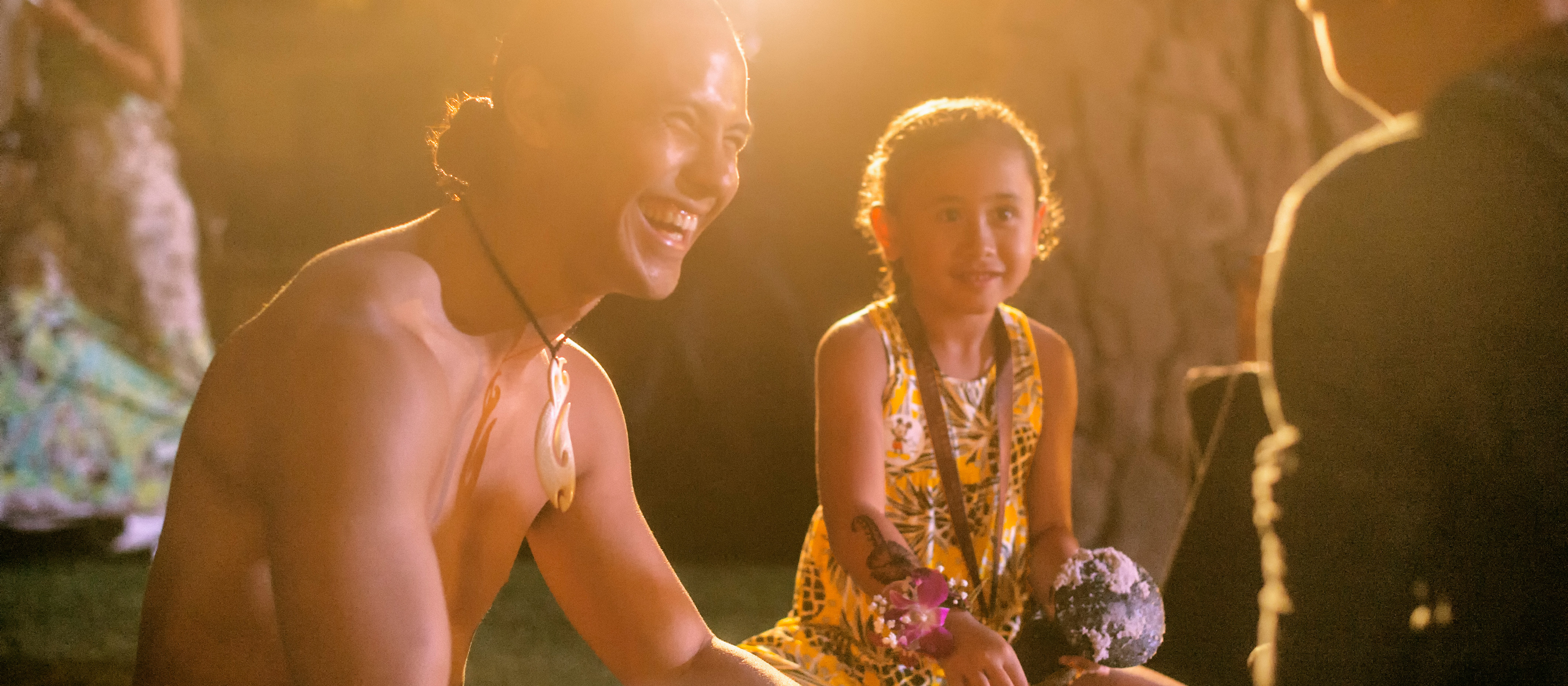 A Ka Wa'a Luau Cast Member wearing a fish hook necklace smiles as he entertains a young girl and her father.