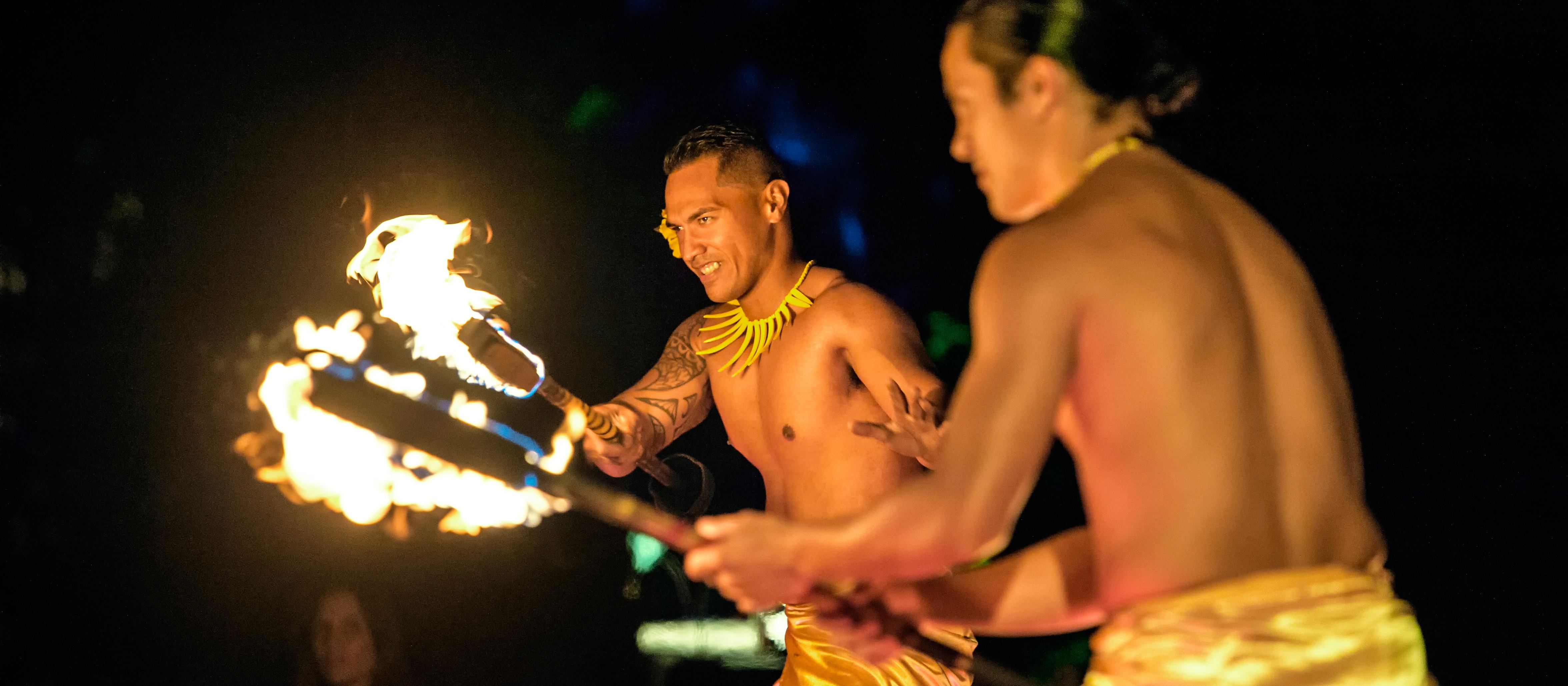 Two Hawaiian men in shiny wraps perform a traditional fire dance for Ka Wa'a Luau guests.