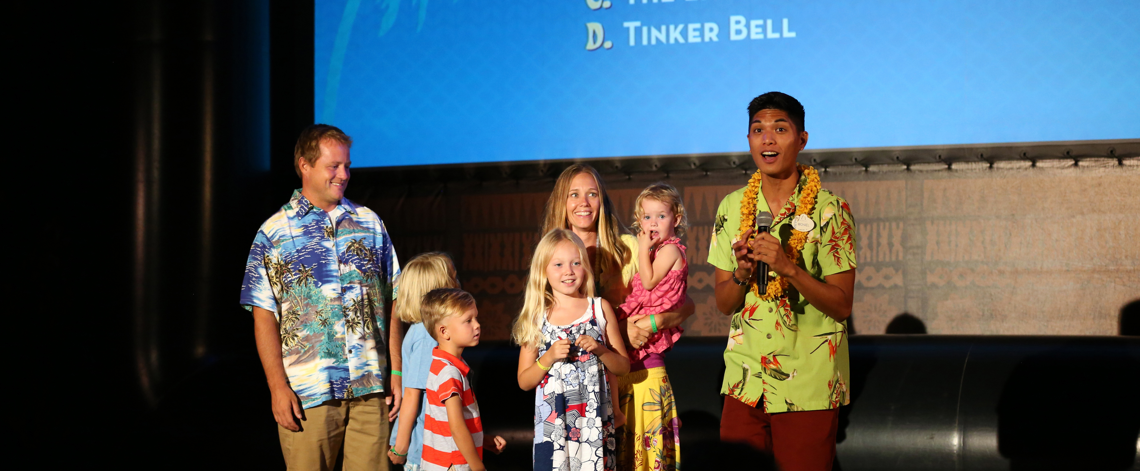 An enthusiastic Cast Member hosts Disney trivia onstage with a family of 6, including 3 girls and a boy