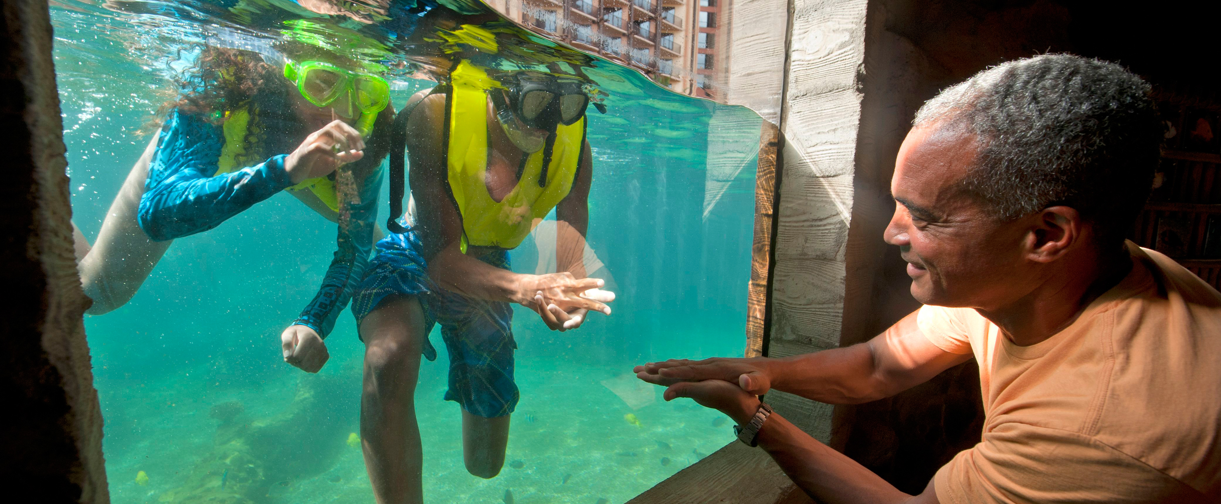 Aquarium glass separates a father from his snorkeling kids as they play rock-paper-scissors together